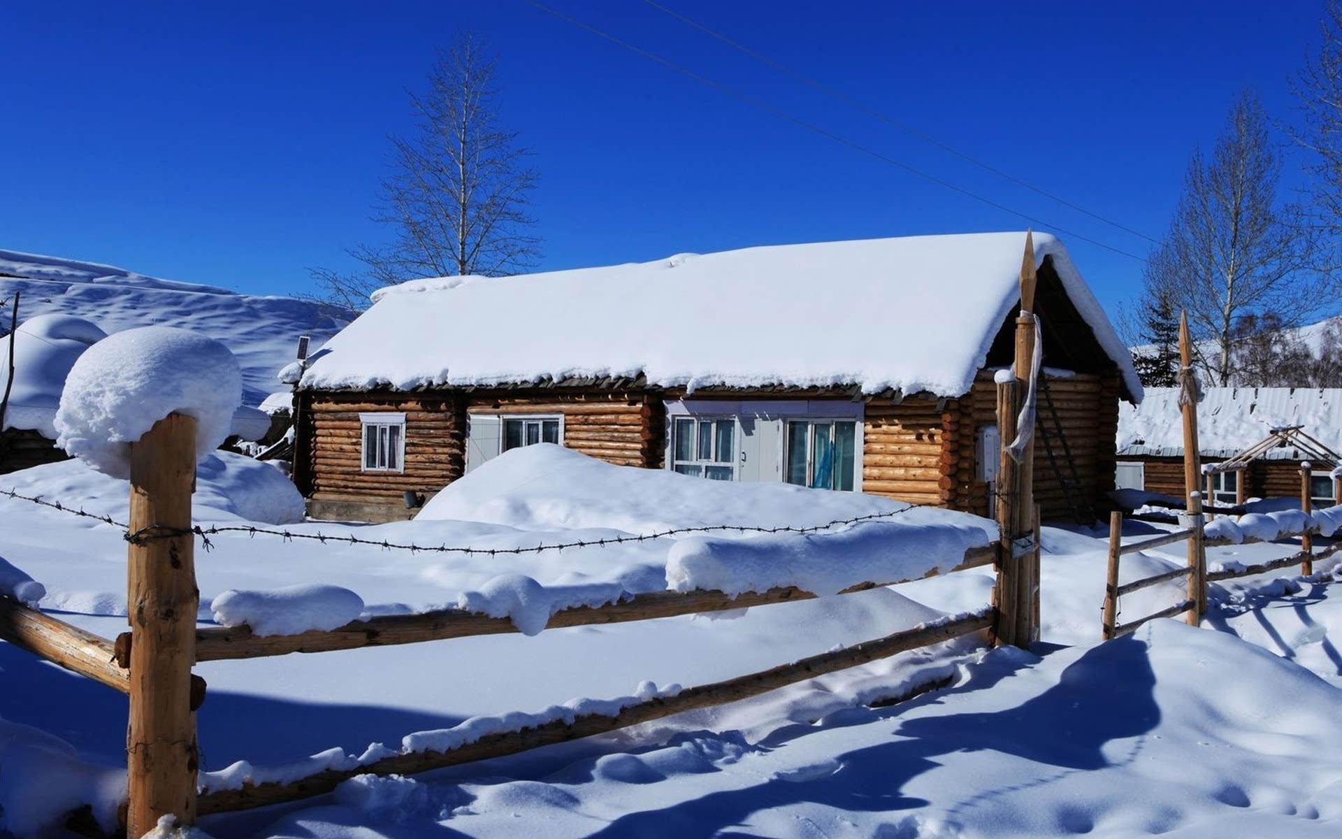 洁白的雪景与黑灰色木屋形成