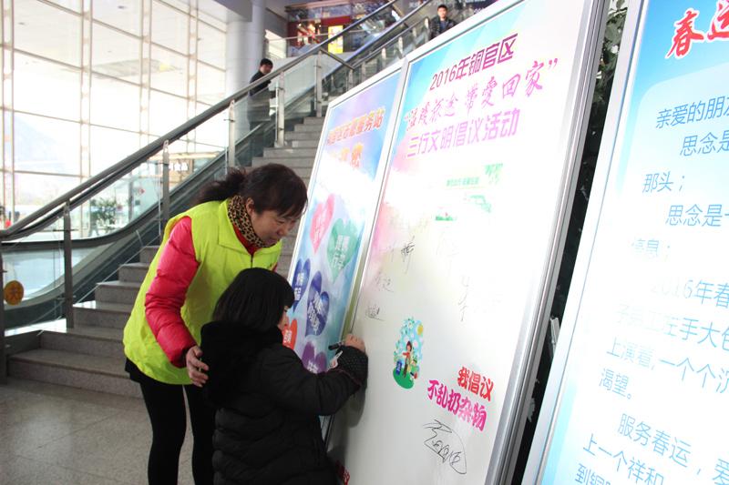 展板上签名 春运期间,铜官区文明办组织志愿者在车站