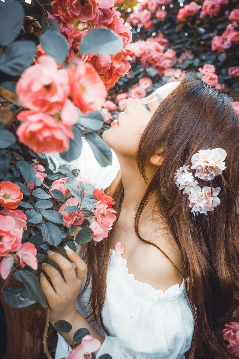 长发丹凤眼美女裸肩群花丛中写真(1)