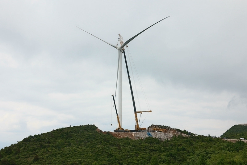 原标题:湖南羊峰山大青山风电场首台风力发电机组吊装成功 北极星风力发电网讯:5月21日,永顺县羊峰山大青山风电场18号机组叶轮与机舱成功对接,标志该项目建设全面进入风力发电机组安装施工阶段。 风力发电机组吊装是一项技术含量高、操作复杂的工程,吊装过程中对天气条件要求极高。首先要依次完成4节塔筒的吊装,然后进行机舱吊装,再在地面完成3片叶片与轮毂的组装,最后将组装好的叶轮升入空中与机舱进行对接。为确保吊装圆满完成,羊峰山大青山风电场项目建设相关单位多次召开协调会议,综合各种因素,进行科学分析和科学部署,出台