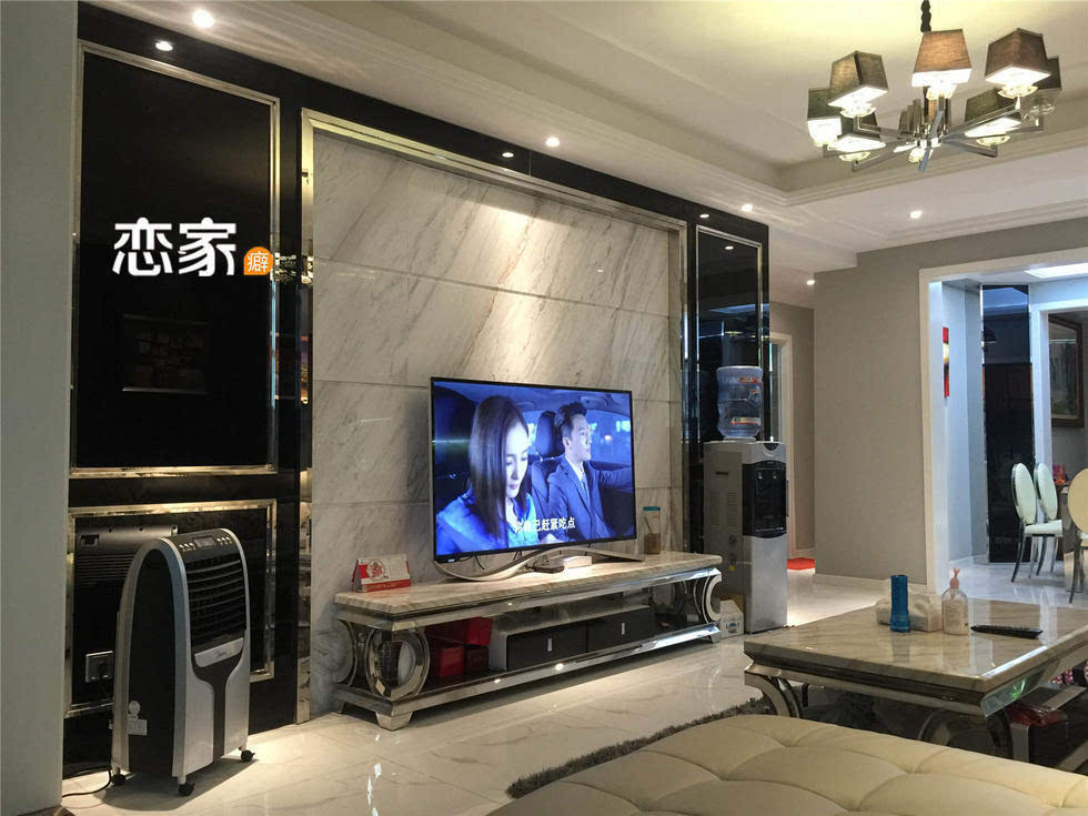 电视墙造型,搭配同样以大理石材质与不锈钢结合的电视柜,揉合出现代