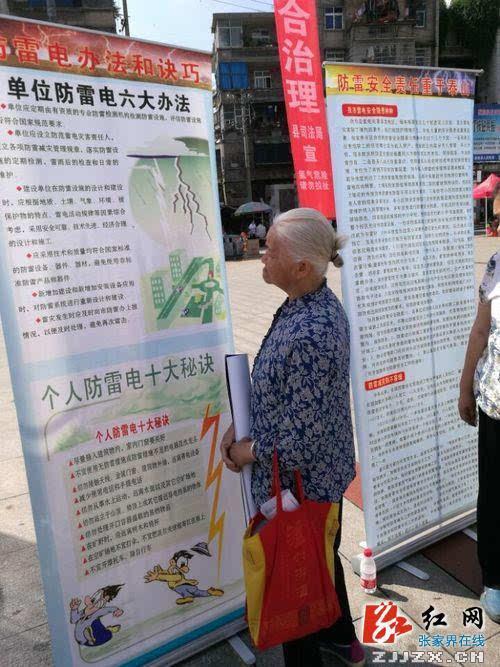 一位老奶奶正在认真阅读气象科普展板上的防灾减灾知识