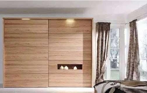 卧室衣柜装修效果图方案分析:想在卧室看电视,又不想牺牲能够摆放家具的墙面,可以选择这款把液晶电视嵌入柜门的款式。集成的设计解决了双重功能,省力又有科技感。靠近电视的移门内部,可以设计放影音设备的层板,即使是在卧室也能体验专业视听效果。 卧室衣柜装修效果图外观提示:安装液晶电视的部分一般都会装饰黑晶玻璃,所以柜体最好选择浅色,否则空间会显得过于沉重。 卧室衣柜装修效果图适合空间特点:不规则房型、开间