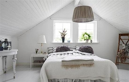 采用的是白色的木板板材进行阁楼卧室的吊顶设计,在两 个斜面的中央