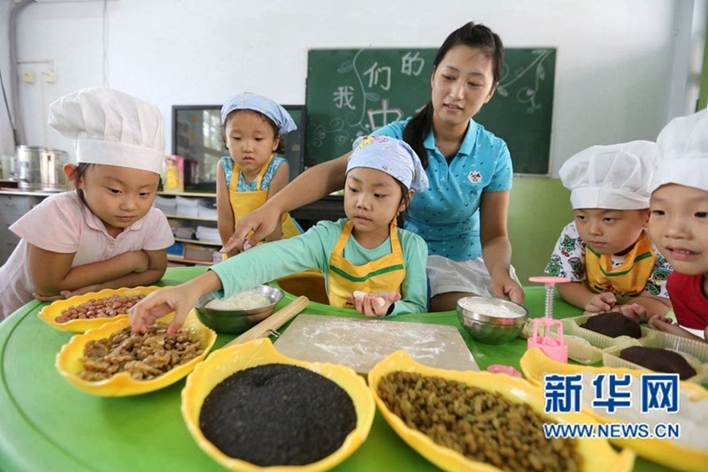 """中心幼儿园开展了""""我们的节日——中秋""""主题活动,教孩子们制作月饼."""