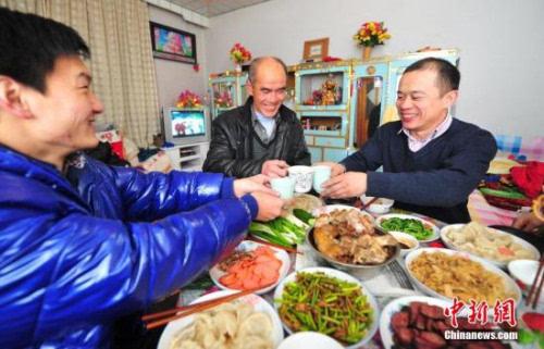 资料图:辽宁省葫芦岛市民在家中与家人享受丰盛的年夜饭.