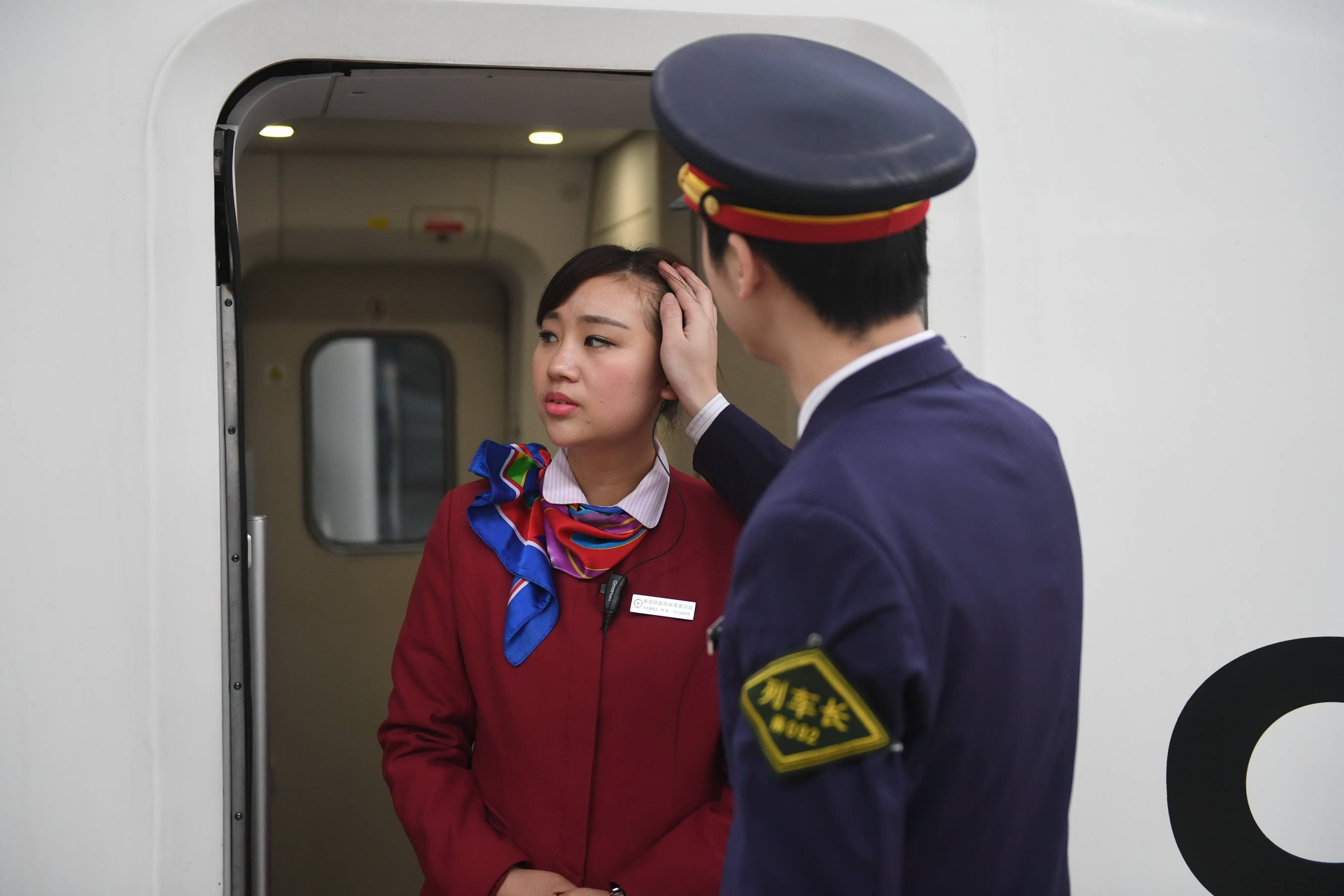 1月25日,在南昌火车站站台,魏星(右)在为妻子整理头发.图片