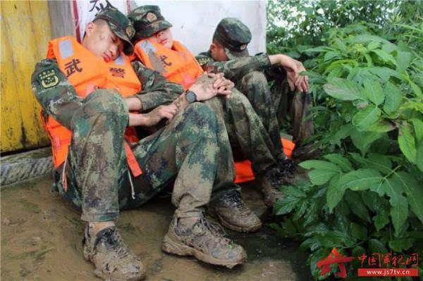几位一线抗洪官兵在完成阶段任务后倚靠墙角歇息 图片来源:中国军视图片