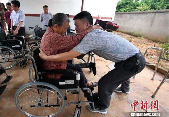 老人扶上轮椅.周亮 摄-江西新余助残行动 免费发放轮椅助行器