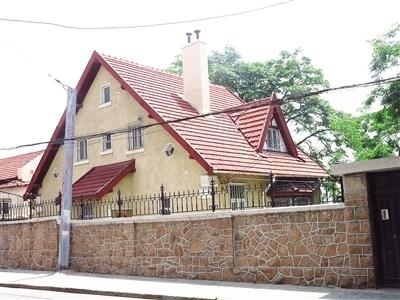 """花岗岩筑基,黄色的粉墙,红瓦斜坡屋顶,屋角的檐下,有类似""""s""""形的花纹"""