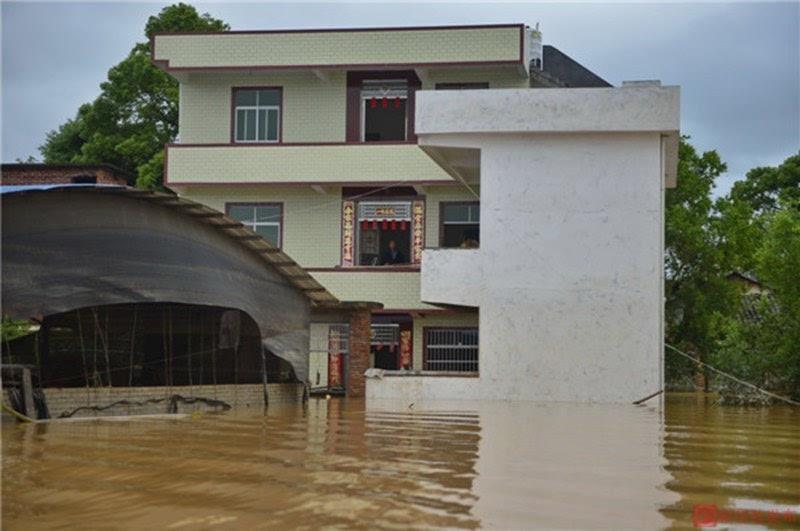 图为5月21日,江西省赣州市于都县车溪乡坝脑村,一名小孩从被洪水侵袭