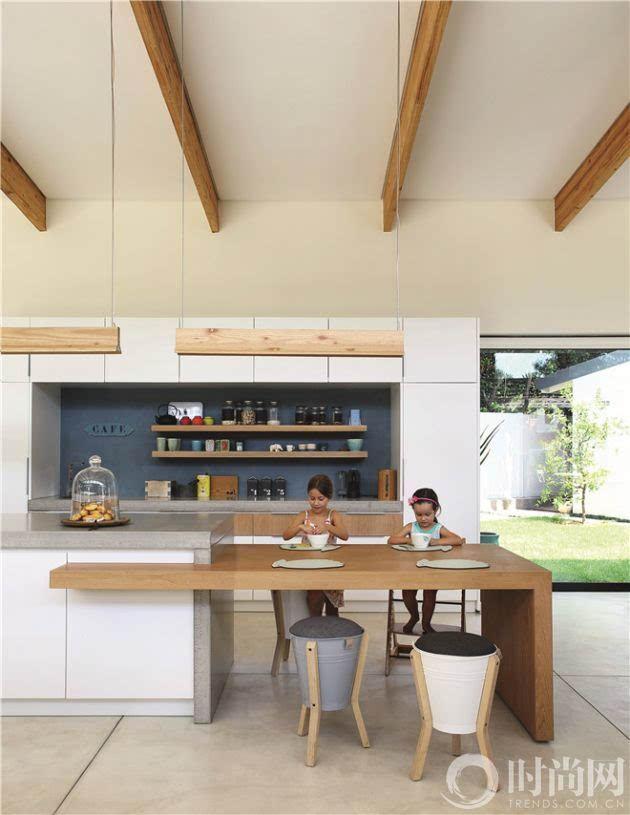 厨房岛台旁加了略低的边桌,后者可以作为早餐桌,或者在此享受一顿亲