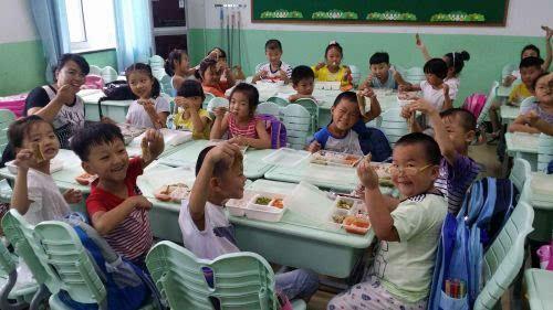 青岛遵义路小学一年级的班主任老师和同学们在教室里围坐在一起,享用