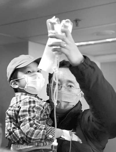 北京儿童医院,家长手拿吊瓶为患儿输液