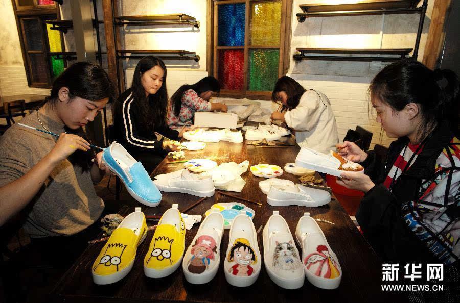 高等专科学校美术系的大学生许岱雅(左一)在用丙烯染料手绘布鞋鞋面.